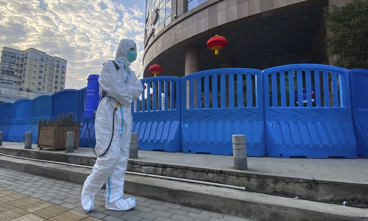 A worker carrying disinfecting equipment walks outside the Wuhan Central Hospital Photo: AP