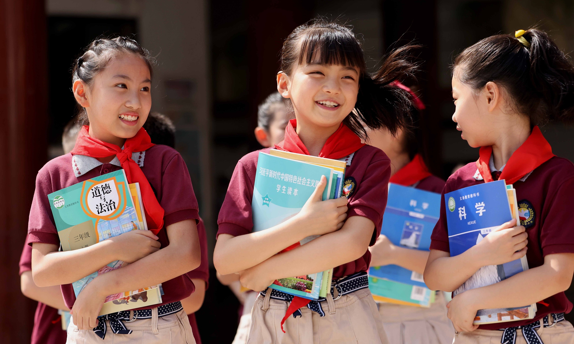 Students run around the Heping Primary School in Yaohai district of Hefei, East China's Anhui Province on Monday, holding new textbooks they have just received. Schools in China will begin the new semester on Wednesday. Photo: IC