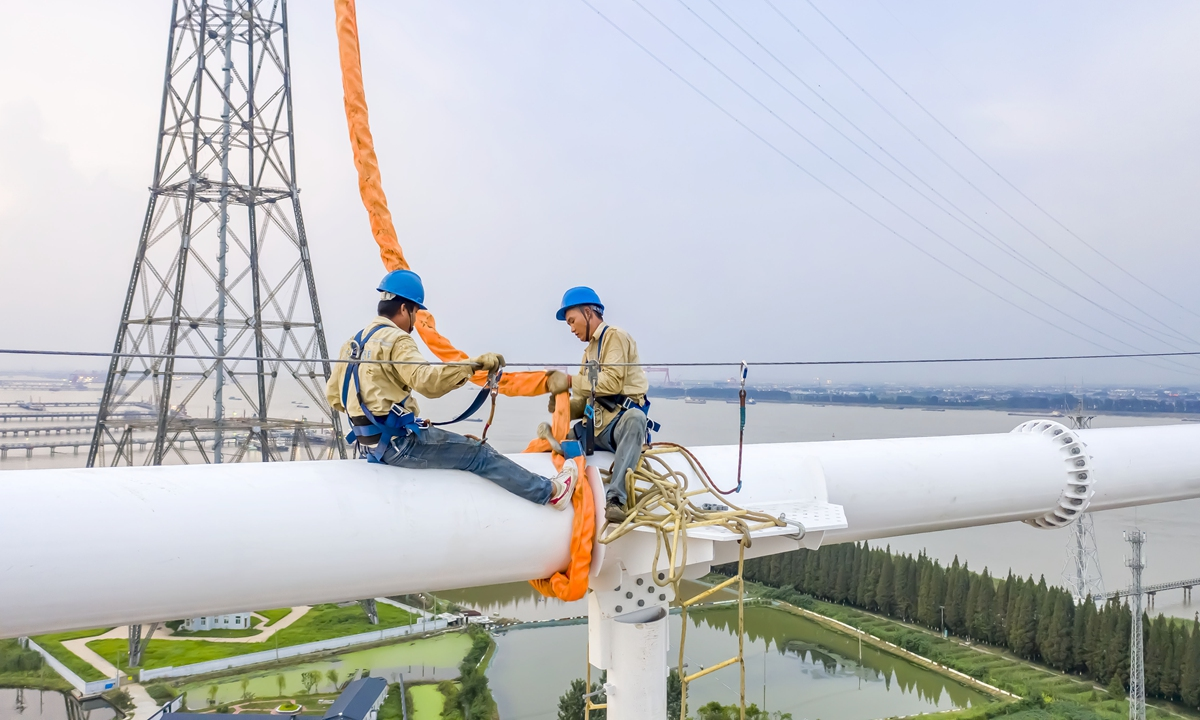 Workers assemble a transmission tower for a bridge across the Yangtze River on Tuesday in East China's Jiangsu Province. The bridge is a major infrastructure project under China's 13th Five-year Plan (2016-20) on electricity development. It will improve the connectivity of the electric grid across the Yangtze River. Photo: cnshphotos