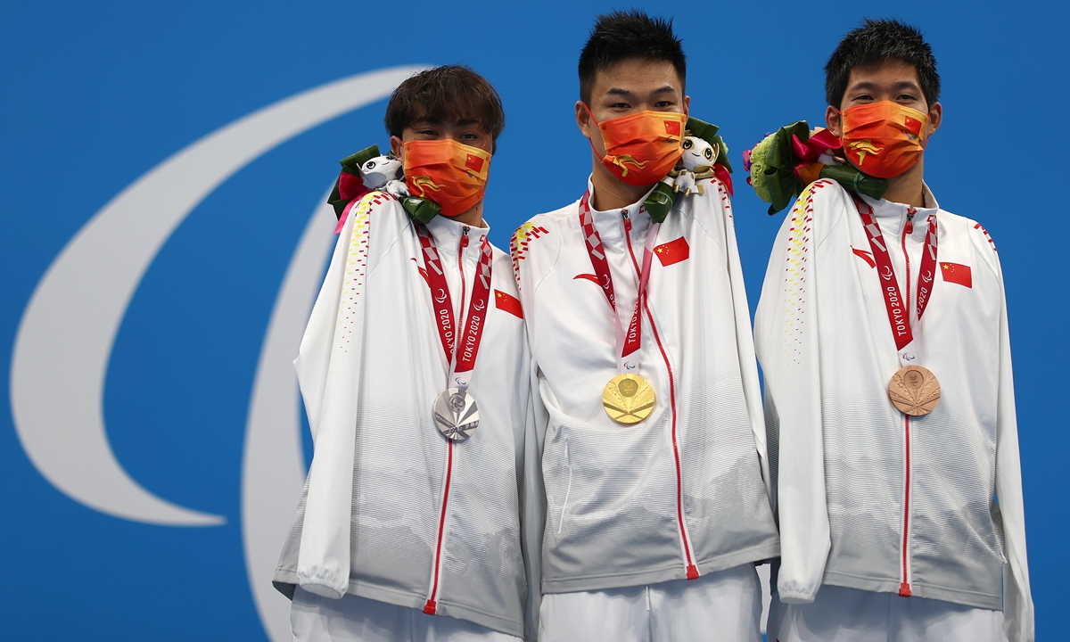 Silver medalist Yuan Weiyi (left), gold medalist Zheng Tao (center) and bronze medalist Wang Lichao pose on the podium after the men's 50 meters freestyle - S5 final. Photo: VCG