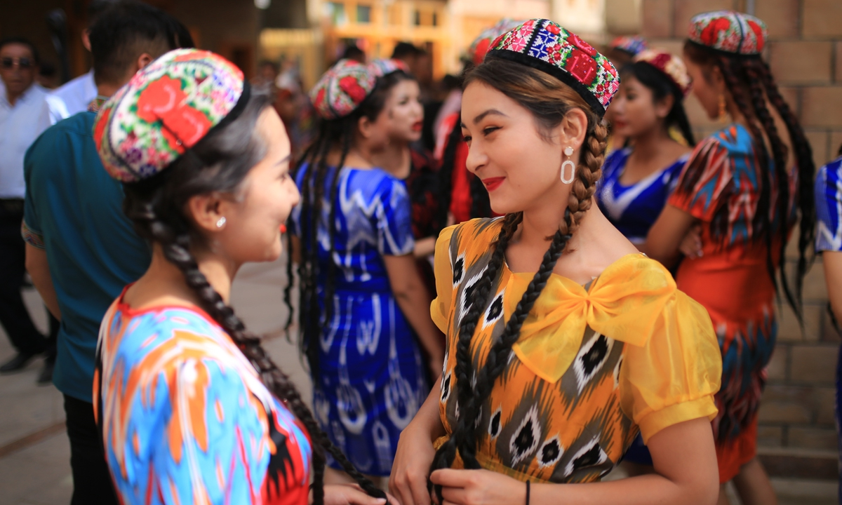 Women in traditional garb chat in Tuancheng during a break from a group dance during the Corban Festival in Hotan. Photo: Liu Xin, Fan Lingzhi/GT