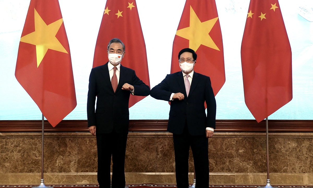 Chinese State Councilor and Foreign Minister Wang Yi (left) bumps elbows to greet Vietnam's Deputy Prime Minister Pham Binh Minh prior to their meeting in Hanoi on Friday. Photo: AFP