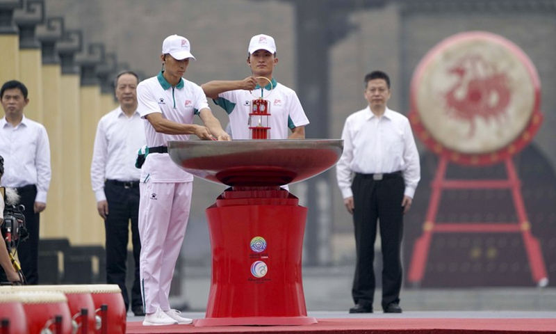 A staff member (4th L) holds the flame lantern before lighting the cauldron prior to the torch relay for China's 14th National Games, 11th National Paralympic Games, and eighth National Special Olympics in Xi'an, Shaanxi Province, Aug. 16, 2021. Photo: Xinhua