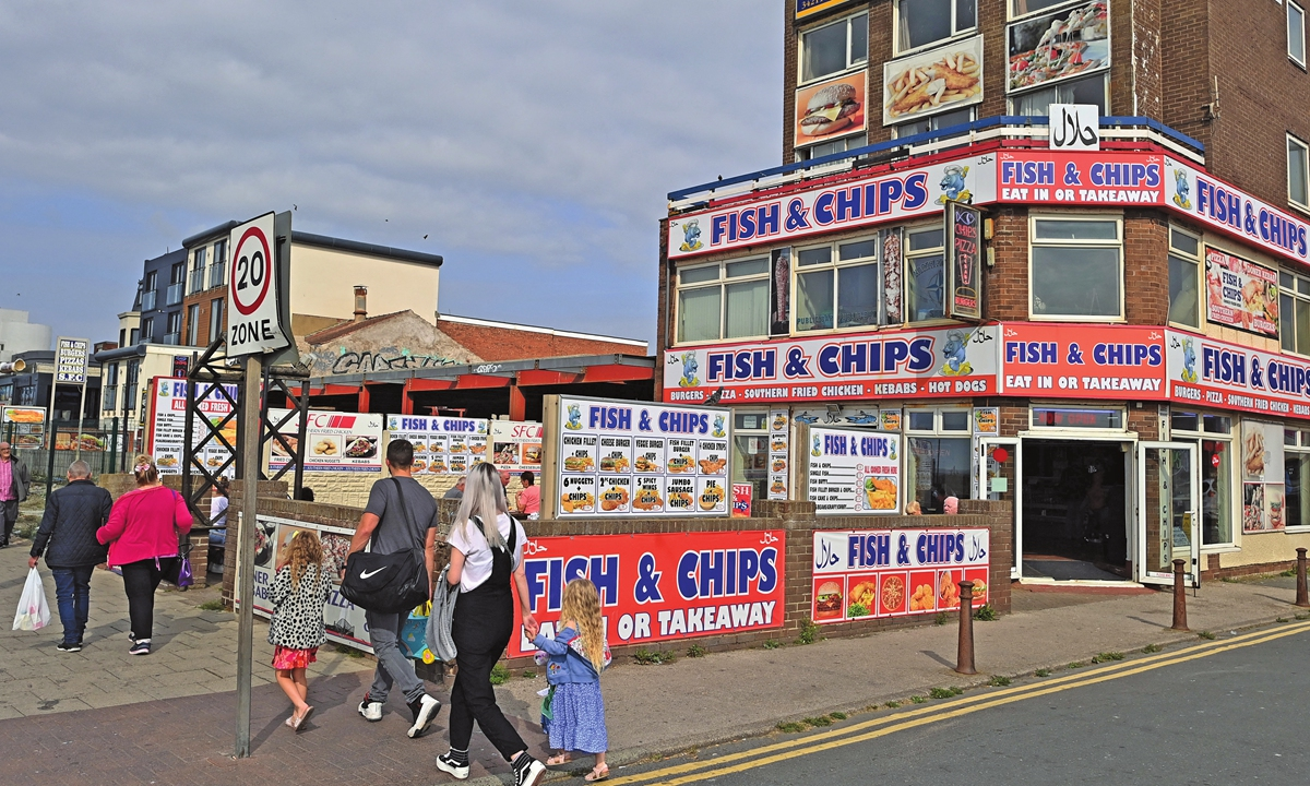 People walk past a fish and chip shop at Blackpool in the UK on September 4, 2021.Photo: AFP