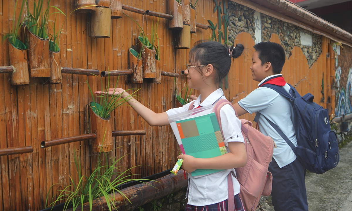 Two primary school students play with water in front of a wall made of bamboo and plants in Shimen village, Ninghai county, on September 7. Photo: Chen Xia/GT