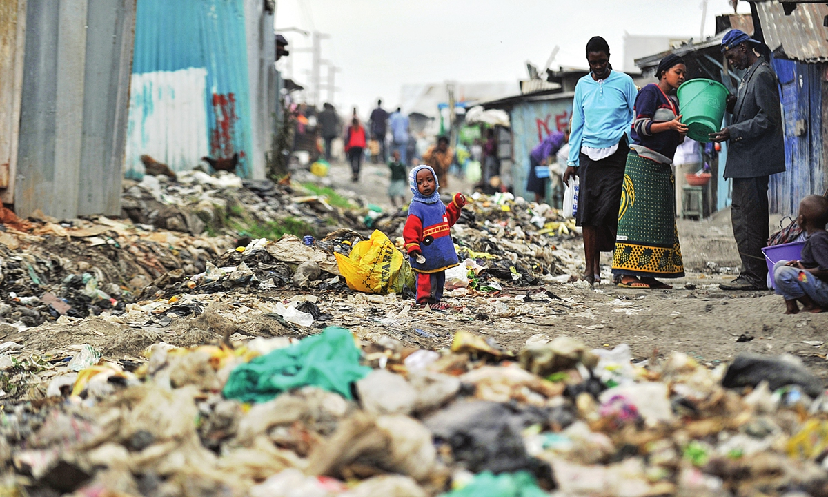 Slum residents stand among strewn rubbish in Nairobi's Mukuru -kwa-Njenga slum in Nairobi, Kenya on July 6, 2010. Photo: AFP