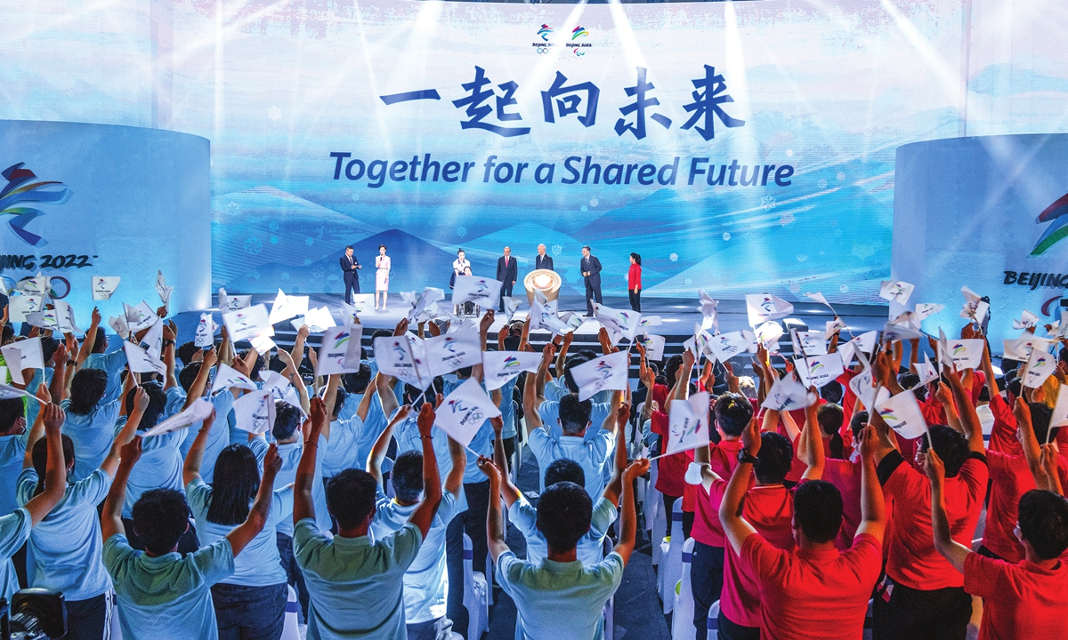 Participants cheer as the motto for the 2022 Beijing Winter Olympics and Paralympics is revealed at a launch in Beijing on Friday. Organizers on Friday announced