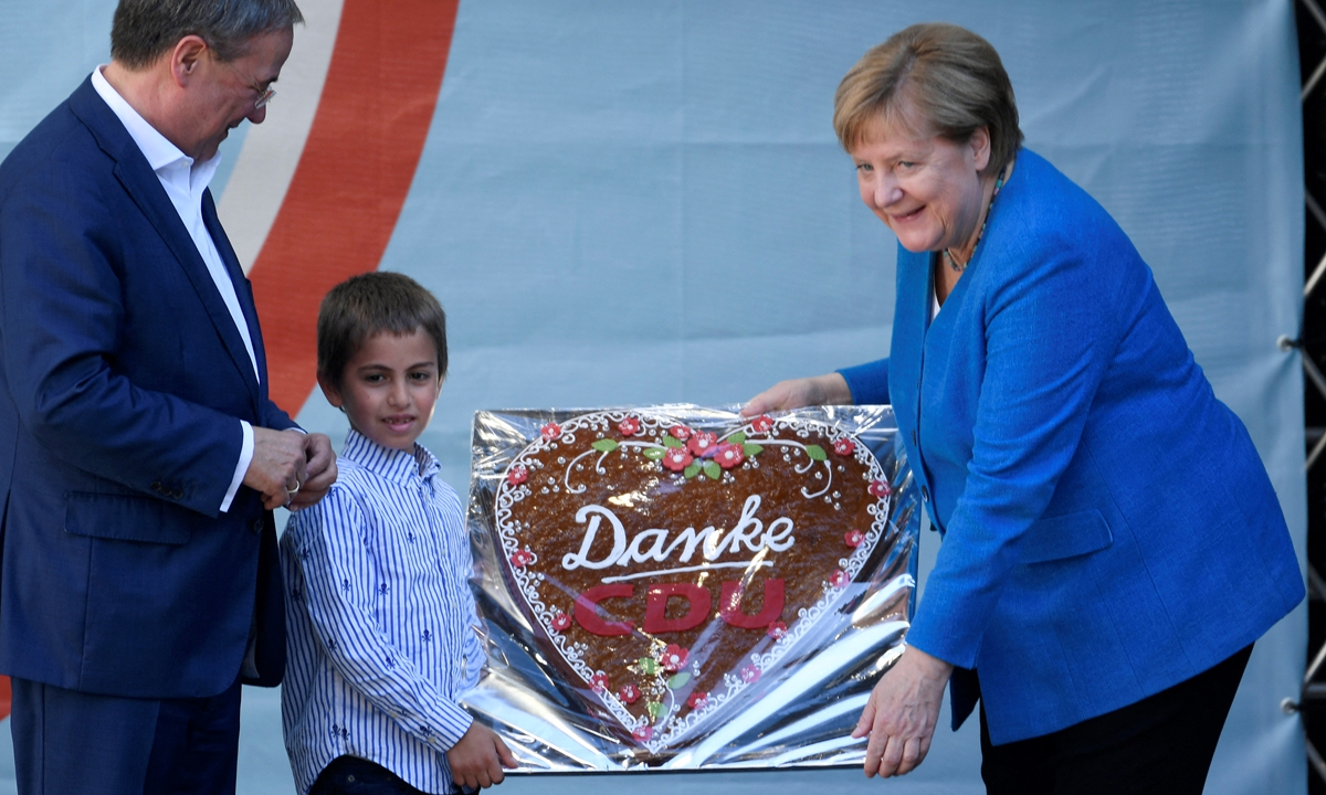 """German Chancellor Angela Merkel (R) is presented with a gingerbread heart with """"Thank you CDU"""" during a campaign rally for Christian Democratic Union leader and chancellor candidate Armin Laschet (L) in Aachen, western Germany, on Saturday. Photo: AFP"""