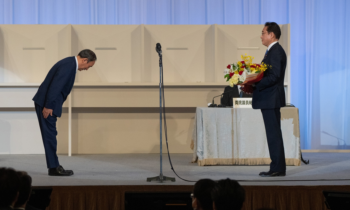 Outgoing Japanese Prime Minister Yoshihide Suga (left) bows to former foreign minister Fumio Kishida after the latter was elected the new leader of the ruling Liberal Democrat Party on Wednesday in Tokyo. Photo: VCG