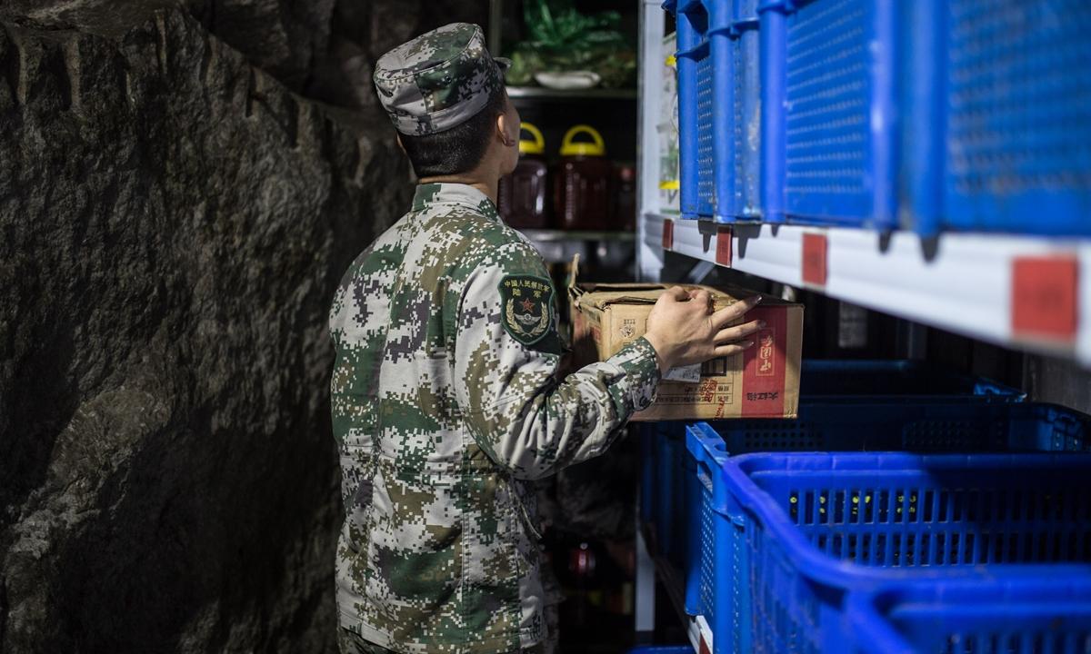 一名士兵在战娘社遗址整理食品储藏室。 照片:单杰/GT