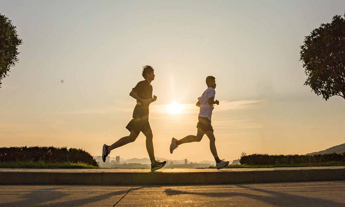 Morning fitness enthusiasts  run against the rising sun at Nanshan Park in Jiujiang, East China's Jiangxi provinceon June 23. Photo:VCG