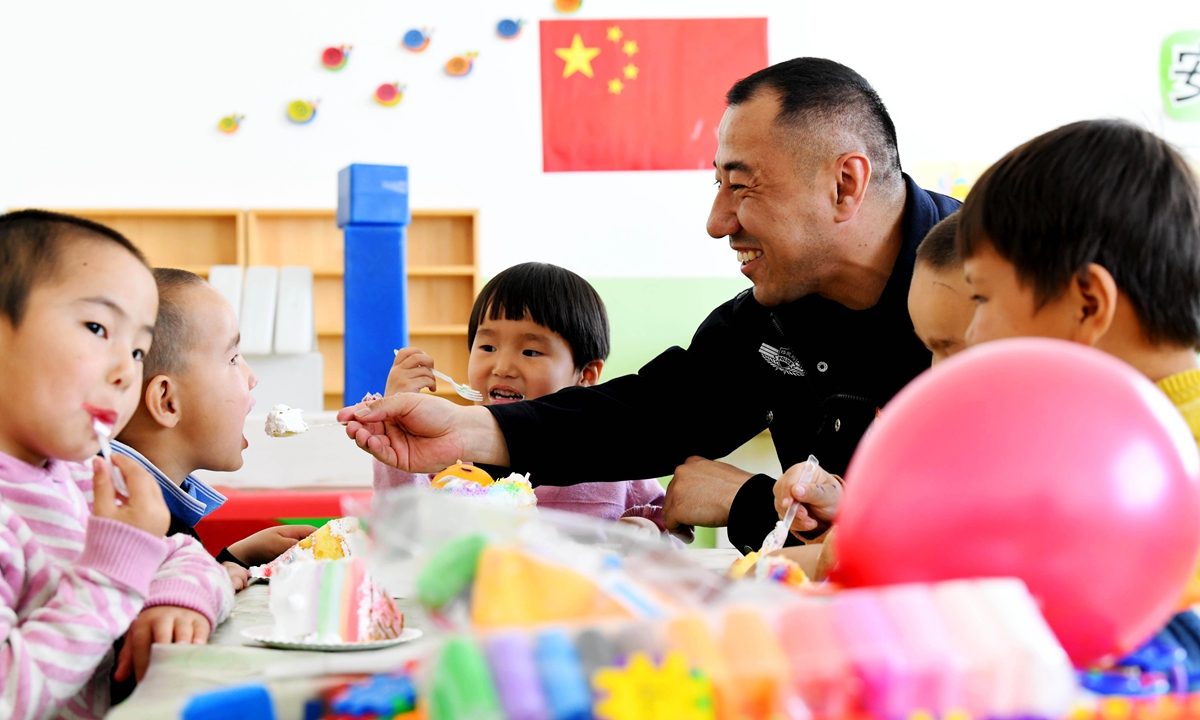 Police officers and children in pastoral areas share a holiday cake to celebrate June 1 Children's Dayon May 30 inChangji Hui Autonomous Prefecture. Photo: IC