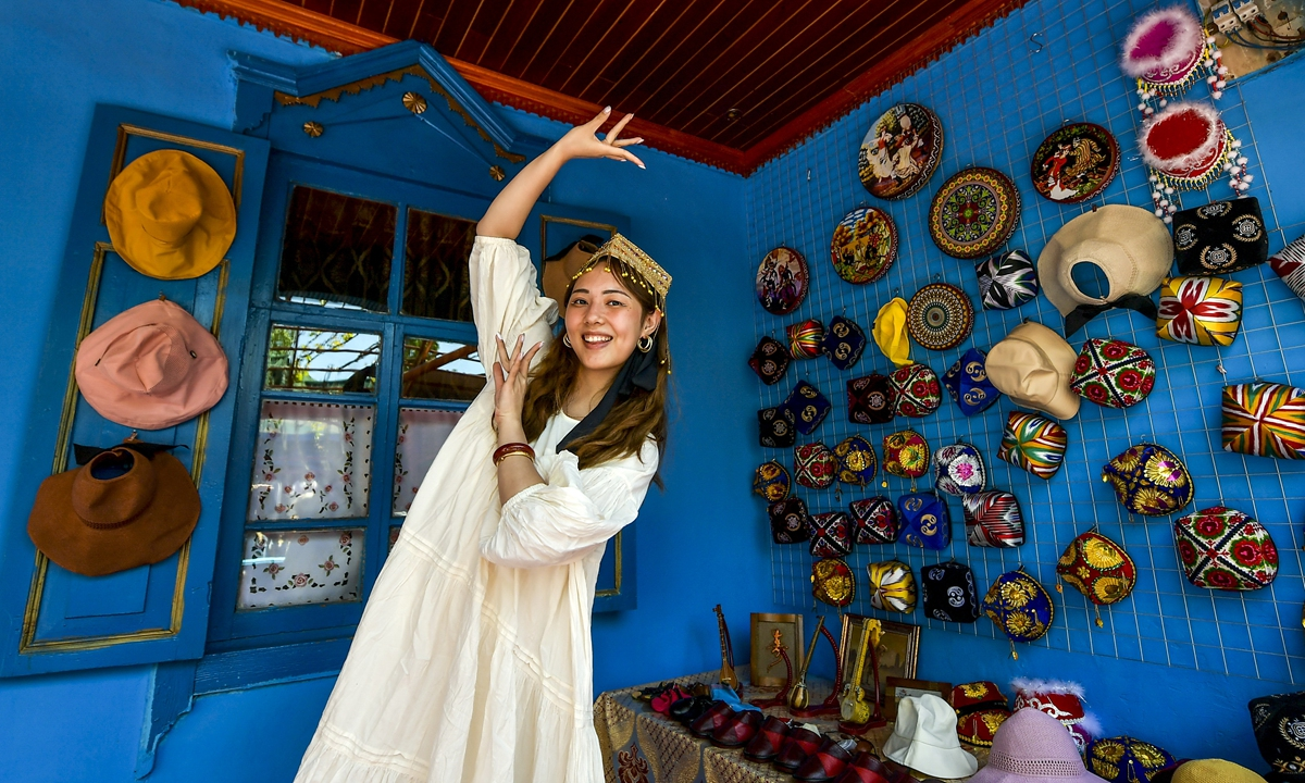 A tourist in an ethnic flower hat dances at a traditional folk housein YiningonMay 4.  Photo:IC
