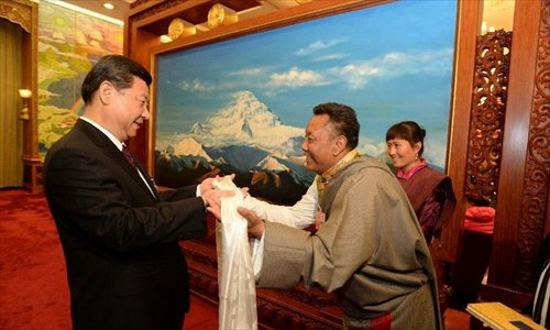 Xi Jinping (left), general secretary of the Central Committee of the Communist Party of China (CPC), receives a hada, a white silk scarf symbolizing respect and blessing, from a deputy to the 12th National People's Congress (NPC) from southwest China's Tibet Autonomous Region, in Beijing, capital of China, March 9, 2013. Xi joined a discussion with the Tibet delegation attending the first session of the 12th NPC in Beijing on Saturday. Photo: Xinhua
