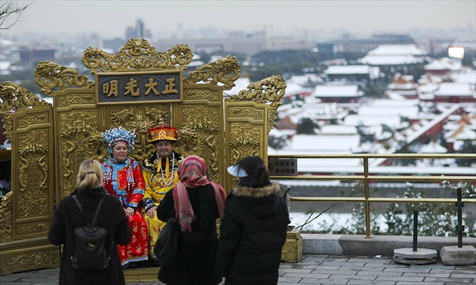 """Foreigners take pictures sitting on a replica """"dragon seat"""" in Jingshan Park in Beijing. Photo: CFP"""